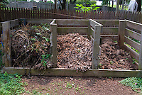Garden Composting with wooden heaps showing decomposing materials in three stages of rot