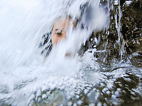 A young local woman looks out from under the spray of a waterfall in Kane'ohe, O'ahu.