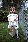 Girl ( 4-5 yrs old) standing, looking for hidden eggs in backyard, with excited, happy face on Easter Sunday, Issaquah, Washington USA MR