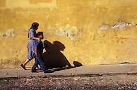 Woman and young boy walking along a street  in the Spanish colonial city of Antigua, Guatemala