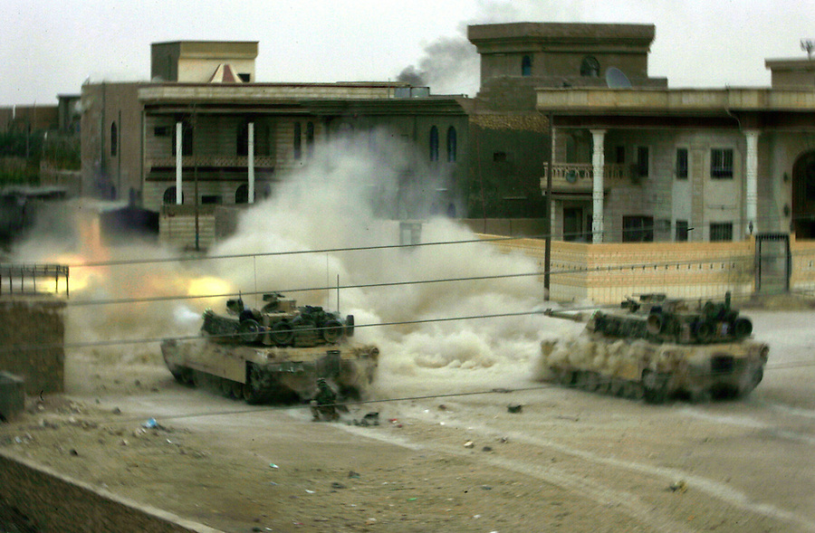 Two tanks attached to Fox Co. 2nd Battalion 1st Marines open fire on a suspected insurgent position during the third day of Operation Steel Curtain, an operation to clear Husaybah (a city on the Iraq-Syrian border) of insurgents on Tues. Nov. 8, 2005.