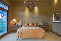 Luxurious large bedroom sparsely furnished is seen with large French doors with outside view