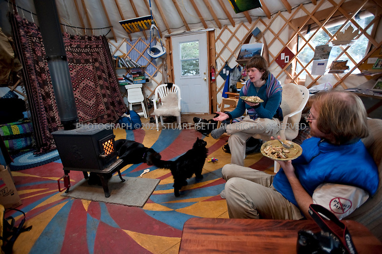 12/11/2009--Seldovia, Alaska, USA..Erin McKittrick (left), with her son, Katmai, strapped to her back, eats lunch with her husband, Bretwood Higman (right) in their yurt in Seldovia, Alaska...The yurt is made by Nomad Shelter in Homer, Alaska, and cost about $14,000. Bretwood Higman ('Hig'), 33 and Erin McKittrick, 30, built it in November, 2008 on land owned by Hig's mother in Seldovia.The yurt is 24' in diameter, the ceiling is over 12' in the middle, 7' around the edge. It has no running water but does have electricity and internet access...McKittrick grew up in Seattle and met Higman, from Seldovia, at Carleton College in 2001. In June 2007, the couple left Seattle for the Aleutian Islands, traveling 4000 miles solely by human power through some of the most rugged terrain in the world; their adventure has recently been published in a book written by McKittrick with Hig's photographs titled, 'A Long Trek Home: 4,000 Miles by Boot, Raft, and Ski'...Together, the couple also run a small environmental non-profit, Ground Truth Trekking, which uses trekking to explore the complexities of natural resource issues. The couple lives with their 10 month old son son, Katmai, in Seldovia, Alaska, a 300 person village just off the end of the road system...©2009 Stuart Isett. All rights reserved.