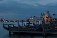 Gondolas moored in front of St Mark's Square or the Piazza San Marco in the evening, and behind, the Punta della Dogana with the Basilica di Santa Maria della Salute, designed by Baldassare Longhena in Baroque style, built 1631-87, Venice, Italy. On the left is the Chiesa del Santissimo Redentore or Church of the Most Holy Redeemer, designed by Andrea Palladio in Renaissance style and consecrated 1592, on Giudecca island. The city of Venice is an archipelago of 117 small islands separated by canals and linked by bridges, in the Venetian Lagoon. The historical centre of Venice is listed as a UNESCO World Heritage Site. Picture by Manuel Cohen
