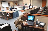 FBI special agent Michael McCoy, of the Baltimore (Maryland) field division, hooks up a system that controls the display of evidence during testimony in the trial of sniper suspect John Allen Muhammad in courtroom 10 at the Virginia Beach Circuit Court in Virginia Beach, Virginia, on October 31, 2003.  McCoy controls 8 monitors and an overhead projector from his laptop and is responsible for playing audio and video tapes of evidence. <br /> Credit: Adrin Snider - Pool via CNP