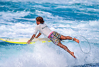 Two Times World Surfing Champion Tom Curren (USA) entering the water at the Hard Rock Cafe event at Haleiwa, Hawaii. The event was the first leg of the Triple Crown of Surfing. circa 1993.  Photo: Joliphotos.com