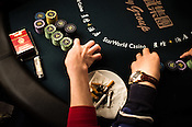 A poker player plays with his chips on the poker table at the Galaxy Macau Hotel in Macau, China.