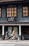 A man cycles past one of the old buildings in Aizuwakamatsu City, Fukushima Prefecture, Japan.  Photographer: Rob Gilhooly