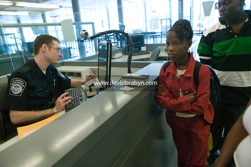 11 April 2006 - New York City, NY - CBP officer Charles Grote (L) processes members of a family from Guyana at a passport control station in Terminal 4 at JFK airport in the Queens borough of New York City, USA, 11 April 2006.