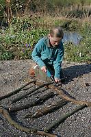 Kinder basteln Klangspiel aus Ästen, Mädchen sägt Äste auf richtige Länge