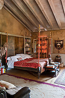 Painted antique panels are used as a headboard for the  four poster bed in this master bedroom