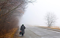 woman walking in foggy day in the ukranian countryside