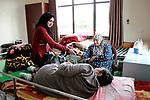 A Palestinian female volunteer presents gift for an elderly Palestinian woman at El Wafa elderly nursing home, in Gaza city on Feb. 12, 2017. El Wafa elderly nursing home was established in 1980 as one of programs of Al-Wafa charity association. El-Wafa hospital was destroy during the 50-day war between Israel and Hamas militants in the summer of 2014 by Israeli forces. Photo by Sana'a Al-Ajez