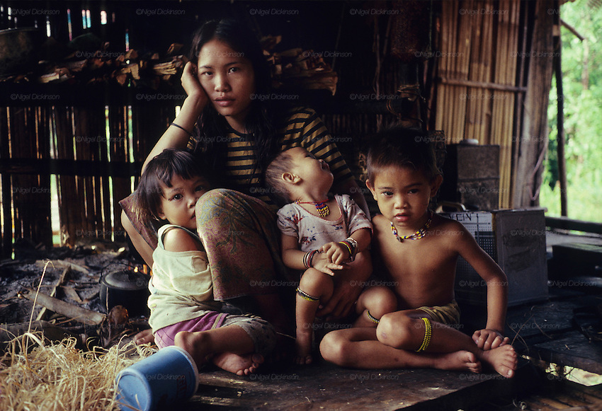 Twenty three years ago: Seventeen year old Den Along (LHS) daughter of Along Sega the renowned resistance fighter, with her daughter Senorita, 1yr old (child in the middle). They are indigenous Penan native people, living as semi-nomadic hunter gatherers. Long Tegang, Limbang district, Sarawak, Borneo 1989<br /> <br /> <br /> PENAN SULAP, MALAYSIA. Sarawak, Borneo, South East Asia.&nbsp; Penan family in sulap settlement. Tropical rainforest and one of the world's richest, oldest eco-systems, flora and fauna, under threat from development, logging and deforestation. Home to indigenous Dayak native tribal peoples, farming by slash and burn cultivation, fishing and hunting wild boar. Home to the Penan, traditional nomadic hunter-gatherers, of whom only one thousand survive, eating roots, and hunting wild animals with blowpipes. Animists, Christians, they still practice traditional medicine from herbs and plants. Native people have mounted protests and blockades against logging concessions, many have been arrested and imprisoned.