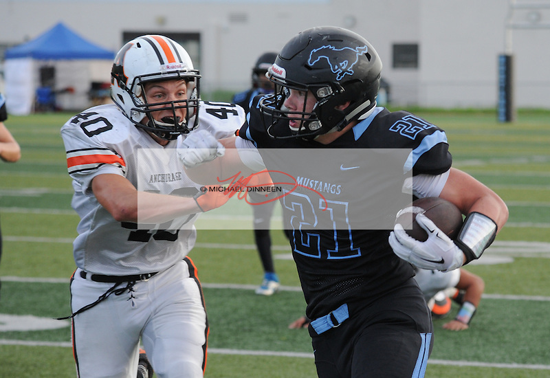 Derryk Snell  runs past West;s Henry Joling at Chugiak Friday, August 27, 2016.  Photo for the Star by Michael Dinneen