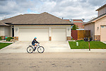 Suburban neighborhood with boy on bicycle.
