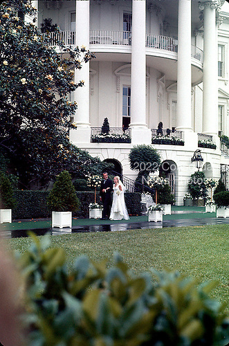 Washington, DC - June 12, 1971 -- United States President Richard M. Nixon, left, escorts his daughter, Tricia, right, to the Rose Garden of the White House in Washington, D.C. on Saturday, June 12, 1971 shortly before she was married to Edward Cox in a White House ceremony.  .Credit: Bill Allen / CNP