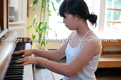 Playing the piano in the canteen, Summerhill School, Leiston, Suffolk. The school was founded by A.S.Neill in 1921 and is run on democratic lines with each person, adult or child, having an equal say.  You don't have to go to lessons if you don't want to but could play all day.  It gets above average GCSE exam results.