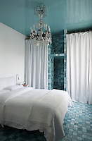 The simplicity of the white cotton bed linen and wardrobe curtains contrasts with the cool blue of the floor tiles and the grandeur of the chandelier
