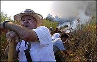 Land owner Bobby Bearden and his employees create a fire line to contain a blaze as it burns through the dry Blue Gurth Swamp.