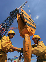 Workers attach steel rods on a crane to lift to a building construction site, Beijing, China
