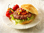 Home made burger in a crusty roll with tomato sweetcorn relish and omion and BBQ peppers photo. Funky Stock Photos.