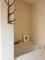 The bath has been built into the wall of this simple bathroom