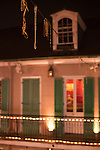 Mardi Gras beads hang from electrical wires on Bourbon Street in New Orleans, Louisiana's French Quarter.  Inside the house, photos of jazz musicians play on TV.