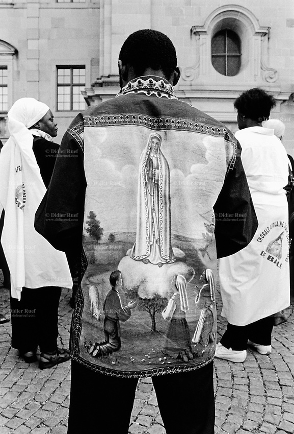 """Switzerland. Canton Schwyz. Einsiedeln Abbey. African pilgrimage. Various religious african communities coming from allover Switzerland and southern Germany celebrate their faith and belief in Jesus Christ. A black man wears a shirt with drawing of """"Our Lady of Fátima """" a title for the Virgin Mary due to her reputed apparitions to three shepherd children at Fátima, Portugal in 1917. The title of Our Lady of the Rosary is also sometimes used to refer to the same apparition. According to religious tradition, Mary was an Israelite Jewish woman and the mother of Jesus. Among her many other names and titles are the Virgin Mary or Blessed Virgin Mary, Mother of God, and Saint Mary in Western churches, Theotokos in Orthodox Christianity, and Maryam, mother of Isa in Islam. Einsiedeln Abbey is a Benedictine monastery in the town of Einsiedeln. The abbey is dedicated to Our Lady of the Hermits, the title being derived from the circumstances of its foundation, for the first inhabitant of the region was Saint Meinrad, a hermit. It is a territorial abbey and, therefore, not part of a diocese, subject to a bishop. It has been a major resting point on the Way of St. James for centuries. 31.08.13 © 2013 Didier Ruef"""
