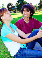 Teenage couple sitting in park laughing.