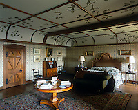 A hand-painted tree motif decorates the ceiling of this large bedroom