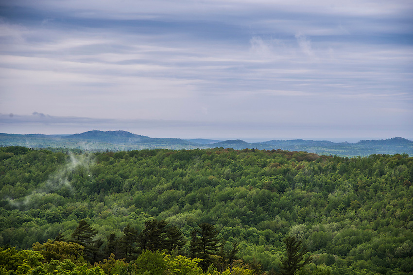 Mist rises from the forested hills of the Huron Mountains near Marquette, Michigan following a rainstorm.