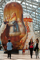 Moscow, Russia, 15/06/2011..People walk through an exhibition of of giant Russian matryoshki, or nesting dolls, in the newly-opened Afimall shopping centre. The dolls, designed by Boris Krasnov, are from 6 to 13 metres high, and each is decorated in a different style of traditional Russian folk art. This doll is in the Fedoskono style, with Russian Imperial porcelain style behind.