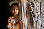 A young girl stands at a temple door, Myanmar