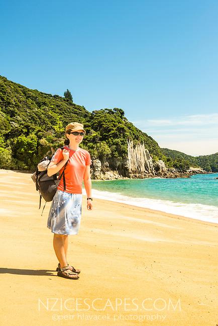 Young woman poses on pristine Anapai Bay on Abel Tasman Coast Track, Abel Tasman National Park, Nelson Region, South Island, New Zealand