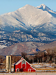 The red barn of the historic Lohr/McIntosh Farm standsout in the early morning light against snow covered Mount Meeker and Long's Peak, Longmont, Colorado
