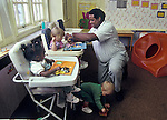 Berkeley CA Caregiver doing puzzles with toddlers, age one, at day care  MR