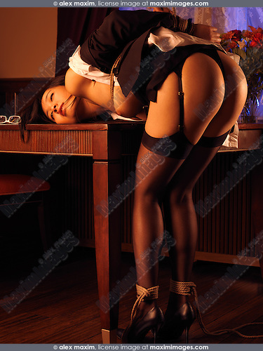 Sexy young woman bending over a table tied up with Japanese rope bondage Shibari