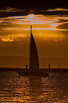 A sailor brings down the sail at the end of the day, backlit by the sunset on the Everett, Washington waterfront.