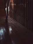 Closeup of bare legs of a woman walking barefoot on a staircase of a dark house