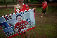 """A girl wearing traditional clothes shows a picture of ousted premier Thaksin Shinawatra outside a temple in the village of Suan Mon near Udon Thani in northeastern Thailand June 25, 2011. Regional leaders of Thailand's red-shirt protest movement held traditional Buddhist ceremony to launch 38 villages designated as """"Red Shirt Village of Democracy."""" The red shirts, supporters of ousted premier Thaksin Shinawatra, have been branding hundreds of villages as red to rally behind Thaksin's sister, Yingluck, who is leading the opposition ahead of July 3 general elections.   REUTERS/Damir Sagolj (THAILAND)"""