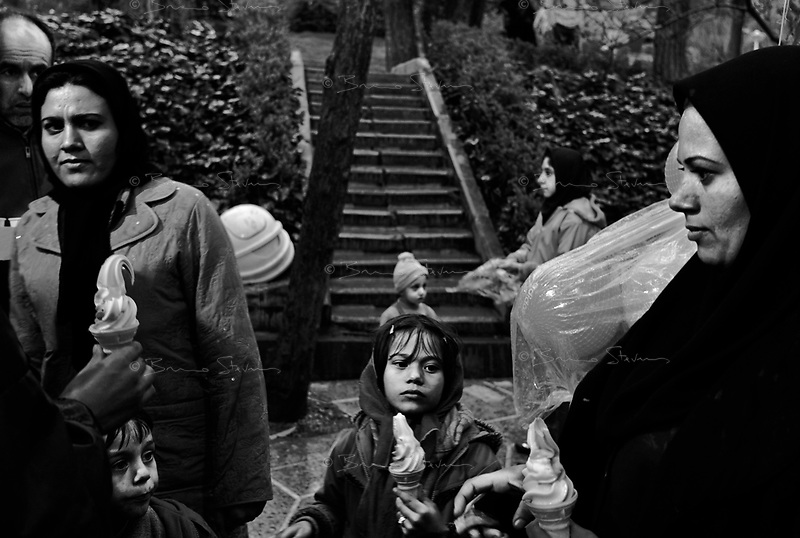"""Teheran, Iran, April 2, 2007.Millions of Iranians of all ages take to the parks and the countryside for picnics on the 13th day of the Iranian new year for """"Sizdah Be Dar"""". Farzaneh, 8, enjoy the holidays last ice-cream."""