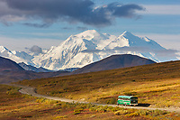 The north and south summits of Mt McKinley are visible from Highway pass as a tour bus travels along the Denali Park road, Denali National park, Alaska.