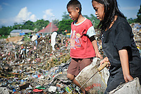 Idirs, 13, and Annie, 8, carrying sacks of plastic and metal waste for recycling at the 'Trash mountain', Makassar, Sulawesi, Indonesia.
