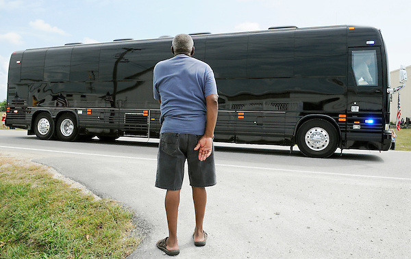 August 17, 2011: Atkinson, Illinois<br /> A bystander watches President Barack Obama's armored bus drive by. It happened during the president's three day swing through rural communities in the Midwest. The bus, colored black with dark tinted windows, made its public debut during this trip. The vehicle was commissioned by the Secret Service at a cost of 1.1 million dollars. The Secret Service dubs the vehicle 'Stagecoach.' &copy;Chris Fitzgerald / Candidate Photos