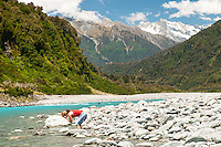 Young woman refreshes in Whataroa River, South Westland, West Coast, New Zealand, MR