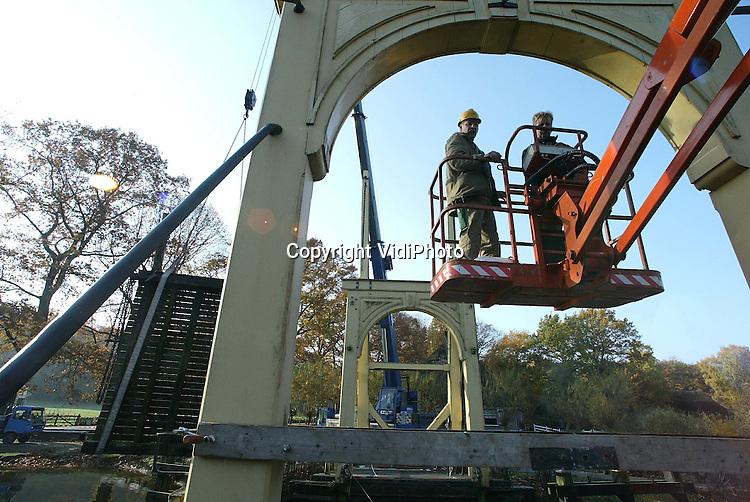 Foto: VidiPhoto..ARNHEM - Het brugdek van de historische Zaanse brug in het Nederlands Openluchtmuseum in Arnhem wordt vernieuwd. Personeel van het museum is met behulp van een kraan begonnen met de demontage van de ophaalbrug, die toegang biedt tot de Zaanse buurt. Eind deze maand moeten de werkzaamheden gereed zijn.