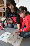 6 year old Sae, in red, (surname withheld), with her mother Mitsue and young sister, at home, with an English learning book written in by Lindsay, near the Nova school where Sae was taught by murdered UK girl Lindsay Ann Hawker, in Koiwa, Tokyo, Japan, on Wednesday, Mar. 28, 2007.