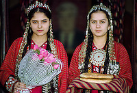 Girl wearing national costume holding traditional welcome gifts of bread and flowers in town of Mary in Turkmenistan