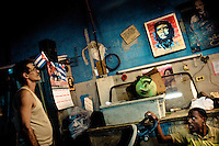 A Cuban worker watches an iconic portrait of the revolutionary leader Che Guevara, hung on the wall of a working room, in Havana, Cuba, 11 February 2009. During the Cuban Revolution, an armed rebellion at the end of the 1950s in Cuba, most of the revolutionary leaders started as no-name soldiers fighting in the jungle. Although the revolutionary leaders, after taking over the power, became autocratic rulers holding almost absolute power and putting the opposition in jail, for some reason Cuban people have never stopped to worship Fidel Castro, Che Guevara, Raul Castro and others. Cubans hang their photos and portraits on the wall in homes, shops and working places even they don't have to. The people of Cuba love their heroes.